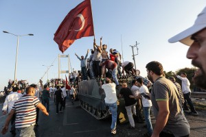 ISTANBUL, TURKEY - JULY 16: Supporters of Turkish President Recep Tayyip Erdogan wave flags as they capture a Turkish Army APC after tens of soldiers involved in the coup attempt in Turkey have surrendered on Istanbul's Bosphorus bridge in Istanbul, July 16, 2016 Turkey. Istanbul's bridges across the Bosphorus, the strait separating the European and Asian sides of the city, have been closed to traffic.Turkish President Recep Tayyip Erdogan has denounced an army coup attempt, that has left atleast 90 dead 1154 injured in overnight clashes in Istanbul and Ankara. (Photo by Gokhan Tan/Getty Images)